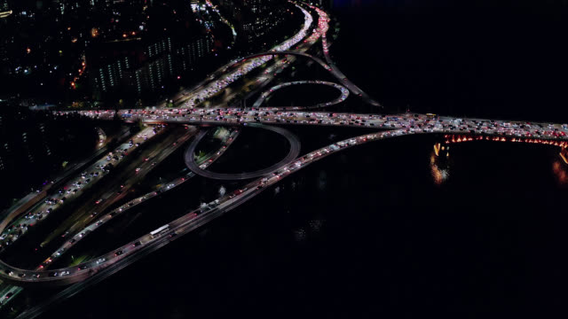 Aerial view of Seoul downtown city skyline with light trails on expressway and bridge cross over Han river at night in Seoul city, South Korea.