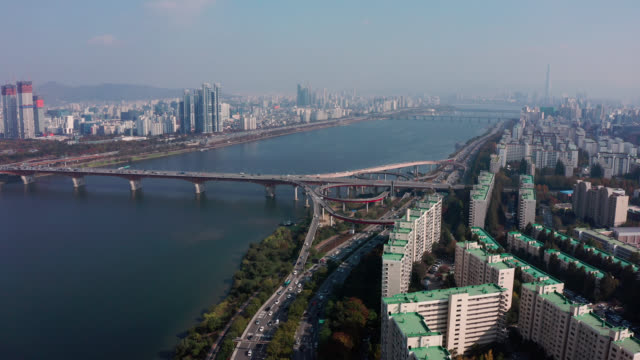 vídeos de stock e filmes b-roll de aerial view of seoul downtown city skyline with vehicle on expressway and bridge cross over han river in seoul city, south korea. - seul