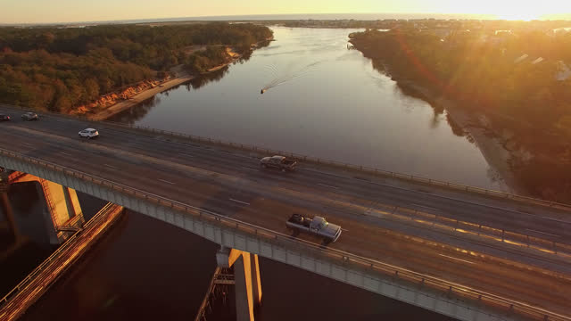 vídeos de stock, filmes e b-roll de zangão. vista aérea do nascer do sol sereno passando sobre a ponte snows cut e canal perto de carolina beach - ponte