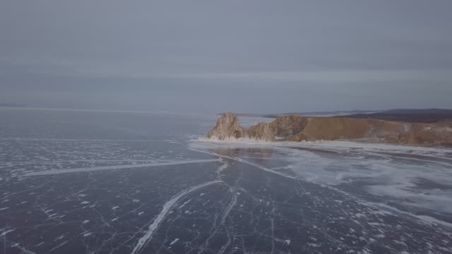 vídeos de stock e filmes b-roll de aerial view of shamanka rock and cape burkhan at sunset on frozen lake baikal, olkhon island in winter. khuzhir, siberia, russia. sunny. landscape of russian natural landmark. drone zoom in - lago baikal