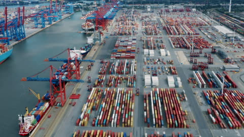Aerial view of shipping containers  in harbor Aerial view of shipping containers stacked in harbor with cranes moving Hamburg, Germany harbor stock videos & royalty-free footage