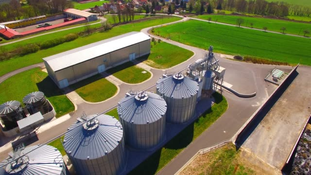 Aerial view of silos, storage tanks for rapeseed. Modern farm in agricultural landscape. Agriculture and environment in European Union. Aerial view of silos, storage tanks for rapeseed. Modern farm in agricultural landscape. Agriculture and environment in European Union. biomass renewable energy source stock videos & royalty-free footage
