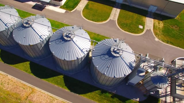 Aerial view of silos, storage tanks for rapeseed. Modern farm in agricultural landscape. Agriculture and environment in European Union. Aerial view of silos, storage tanks for rapeseed. Modern farm in agricultural landscape. Agriculture and environment in European Union. biofuel stock videos & royalty-free footage