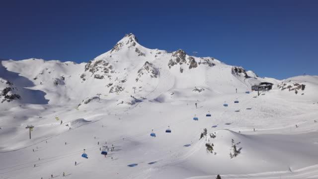 vídeos de stock, filmes e b-roll de vista aérea de esquiadores em pistas de esqui em obertauern estação de esqui, salzburger land of austria. - áustria