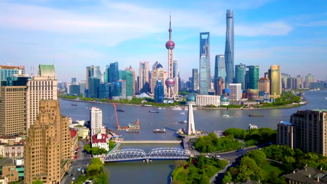 Aerial view of skyscraper and high-rise office buildings in Shanghai Downtown with Huangpu River, China. Financial district and business centers in smart city in Asia at noon with blue sky.