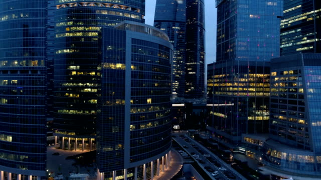 Aerial view of skyscrapers at midnight. Business offices windows.
