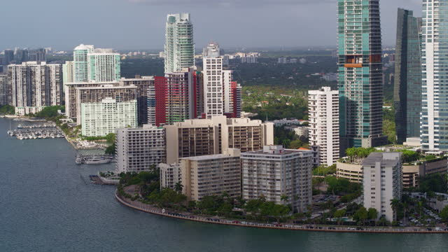 Aerial view of skyscrapers, office and residential buildings, and condo apartments in Downtown Miami in the early morning. Drone-made video footage with panning camera motion. Aerial view of Downtown Miami in the early morning. 4K UHD drone-made B-Roll footage. ocean front properties stock videos & royalty-free footage