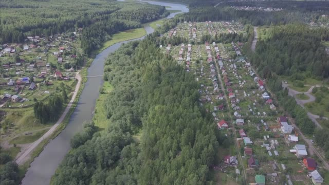 aerial view of small town near forest. clip. aerial view of the town in a wooded area with river - livigno video stock e b–roll