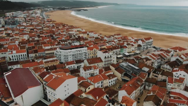 aerial view of small town with bright buildings near ocean - vídeo