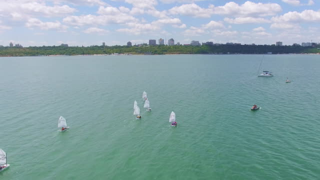 Aerial view of small yachts training at sea Aerial view of youth yachts regatta training at sea with city on background regatta stock videos & royalty-free footage