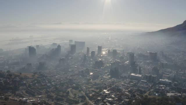 4k luftbild von smog und verschmutzung, die bei sonnenaufgang über dem stadtzentrum von kapstadt, dem hafen und den umliegenden vororten hängen - aerial overview soil stock-videos und b-roll-filmmaterial