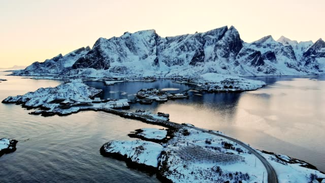 vídeos de stock e filmes b-roll de aerial view of snow mountain with fishing village in arctic ocean at sunset - lofoten