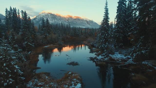 stockvideo's en b-roll-footage met luchtfoto van de (drone) van sneeuw bedekte evergreens, rivier en bergen bij zonsondergang - sneeuwkap