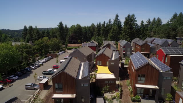 ultra hd 4k aerial view of solar panels on building rooftops - grow community bainbridge island, washington, usa - solar panels stock videos & royalty-free footage
