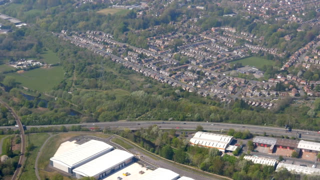 Aerial view of Stockport from colorful football pitches to wastewater plant