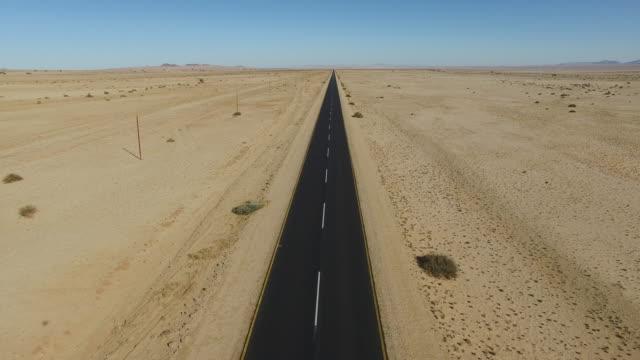 vídeos de stock e filmes b-roll de 4k aerial view of straight tar road through the namib desert - reto descrição física