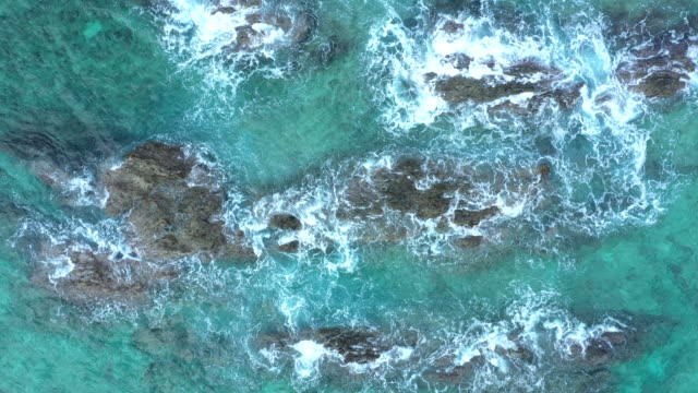 Aerial view of strong wave beating the rocks