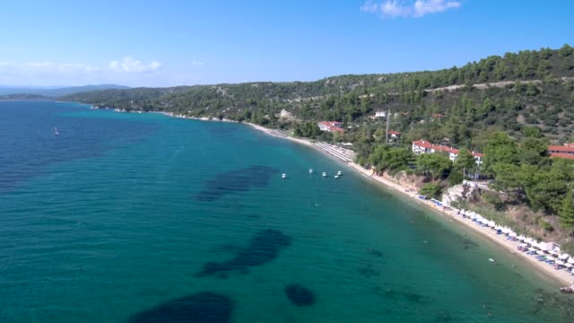 Aerial view of stunning blue beach below a hill in the area of Halkidiki Greece, move forward and down by drone