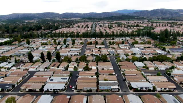 vidéos et rushes de vue aérienne du quartier de maisons emballées de banlieue avec la route - hlm