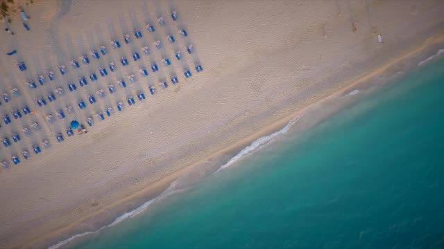 luftaufnahme der sonnenliegen am strand in kathisma, insel lefkada, griechenland. - sun chair stock-videos und b-roll-filmmaterial