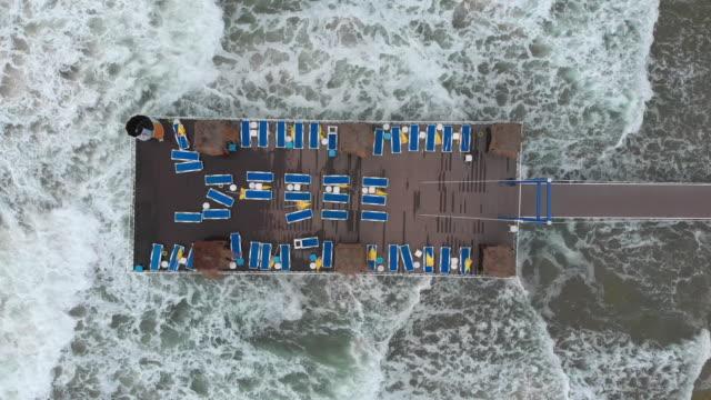luftaufnahme von sonnenliegen auf einer werft in einem strand bei stürmischem wetter - rechteck stock-videos und b-roll-filmmaterial