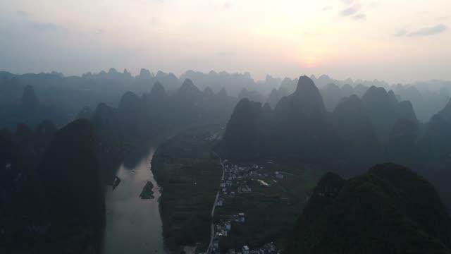 luftaufnahme des sonnenuntergangs über die karstgebirgslandschaft von yangshuo, provinz guanxi, china. - provinz guangxi stock-videos und b-roll-filmmaterial