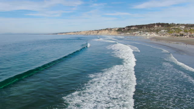 Aerial view of surfers enjoying waves in La Jolla with the scripps pier institute of oceanography on the background