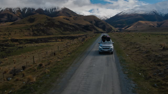 Aerial view of SUV driving in the desert towards snowy mountain peaks in New Zealand Aerial view of SUV with cargo on roof driving on straight highway country desert road in New Zealand mountains sports car stock videos & royalty-free footage
