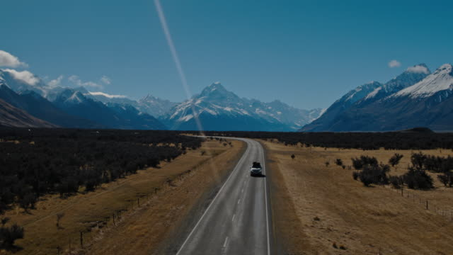 Aerial view of SUV driving in the desert towards snowy mountain peaks in New Zealand Aerial view of SUV with cargo on roof driving on straight highway country desert road in New Zealand mountains alternative fuel vehicle videos stock videos & royalty-free footage