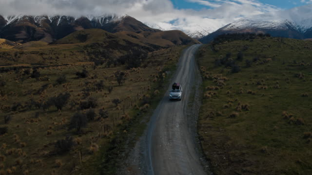 Aerial view of SUV driving in the desert towards snowy mountain peaks in New Zealand video