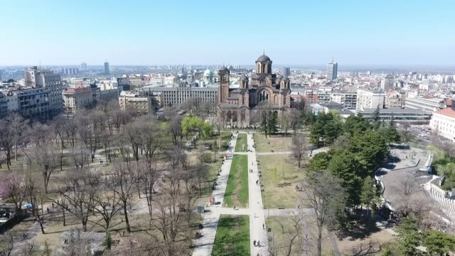 aerial view of tasmajdan park in the belgrade city the capital of serbia with serbian orthodox church of saint marko  building and people walking view from above - белград стоковые видео и кадры b-roll