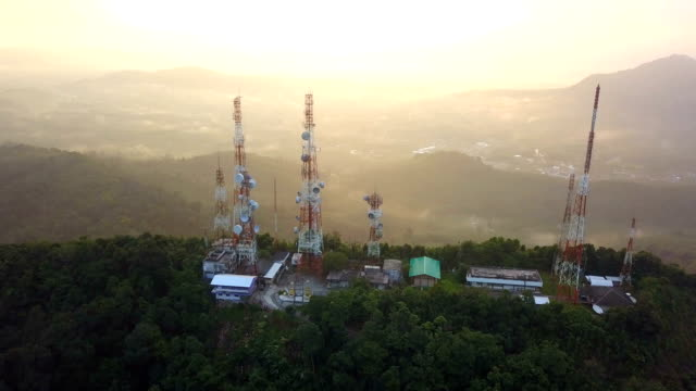 Aerial view of Telecommunication mast TV antennas at sunrise on mountain over the city