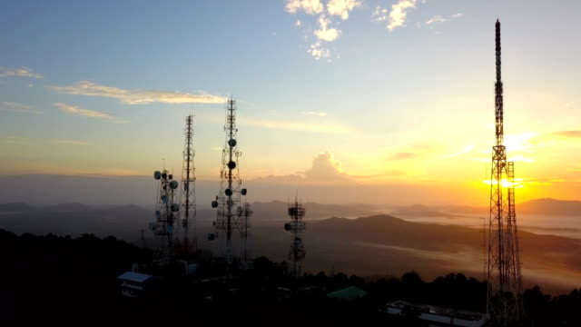 Aerial view of Telecommunication mast TV antennas at sunrise on mountain over the city video