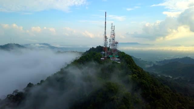 flygfoto över telekommunikation mast tv antenner med dimmigt på berg över staden - antenn telekommunikationsutrustning bildbanksvideor och videomaterial från bakom kulisserna