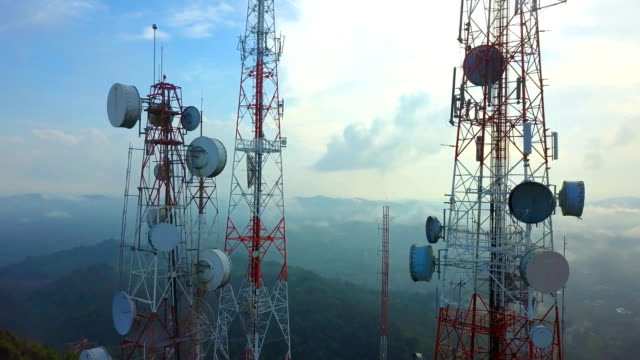 aerial view of telecommunication mast tv antennas with foggy on mountain over the city - спутниковая антенна стоковые видео и кадры b-roll