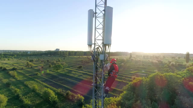 aerial view of telecommunications tower, technician in safety vest and hard hat uses mobile phone on top of cellular antenna - antena filmów i materiałów b-roll