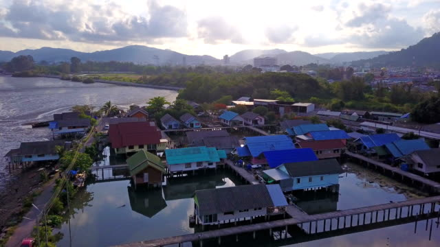 Aerial view of Thai traditional Asian fishing village near sea beach. Floating houses at sunset background in rural area, Phuket island. Thailand. Top view
