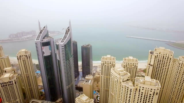 aerial view of the array of skyscrapers facing the sea in the small fog. dubai, united arab emirates - dubai architecture stock videos & royalty-free footage