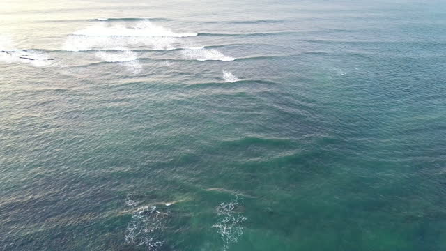 Aerial view of the Atlantic ocean with approaching waves, white spray