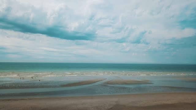 vídeos de stock e filmes b-roll de aerial view of the beach and the rising tide - linha do horizonte sobre água