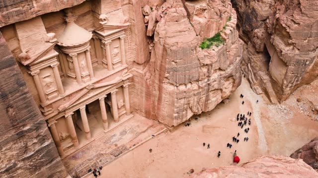 Aerial view of the beautiful Al Khazneh (The Treasury) with tourists admiring it from below. Petra is a historical and archaeological city in southern Jordan. Aerial view of the beautiful Al Khazneh (The Treasury) with tourists admiring it from below. Petra is a historical and archaeological city in southern Jordan. treasury stock videos & royalty-free footage