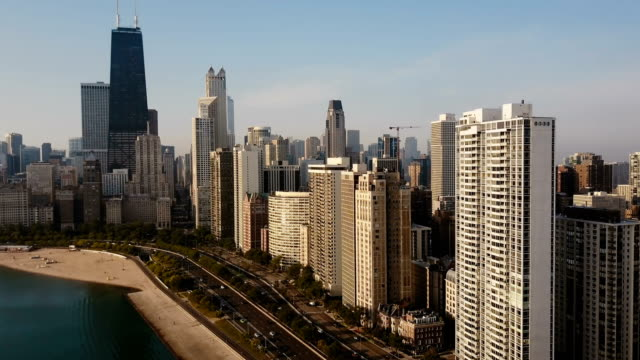 Aerial view of the beautiful Chicago cityscape. Drone t flying away from skyscrapers and Michigan lake, acceleration Aerial view of the beautiful Chicago cityscape in the morning. Drone flying away from the skyscrapers and Michigan lake. Scenic landscape of the busy downtown in dawn, acceleration. chicago architecture stock videos & royalty-free footage