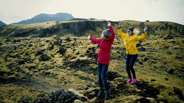 Aerial view of the beautiful landscape in Iceland, lava field covered moss. Two woman dance and jump on the mountain