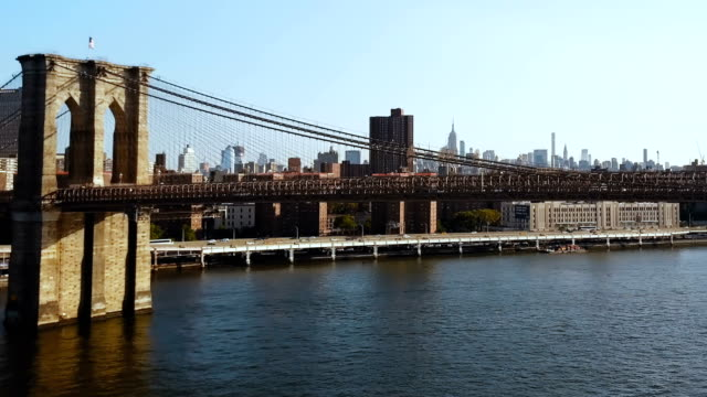 Aerial view of the Brooklyn bridge through the East river on Manhattan, New York. Drone flying over the traffic road video