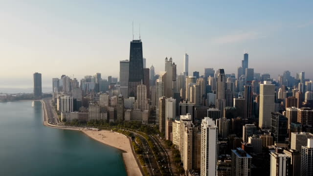 vídeos de stock e filmes b-roll de aerial view of the chicago, america. busy downtown, city centre on the shore of the michigan lake on the dawn - margem do lago