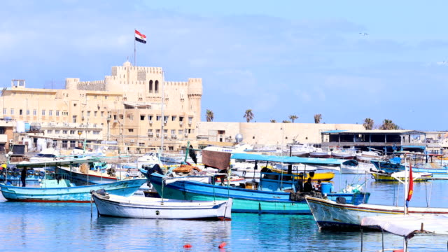 aerial view of the citadel of qaitbay from the mediterranean sea in alexandria, egypt. a lots of fishing boats in front of the citadel, under blue sky. - египет стоковые видео и кадры b-roll