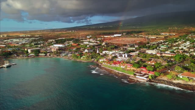 Aerial view of the city of Kailua Kona during sunset Aerial view of the city of Kailua Kona during sunset with stormy sky and rainbow on the background, Big Island, Hawaii. Camera orbits clockwise big island hawaii islands stock videos & royalty-free footage