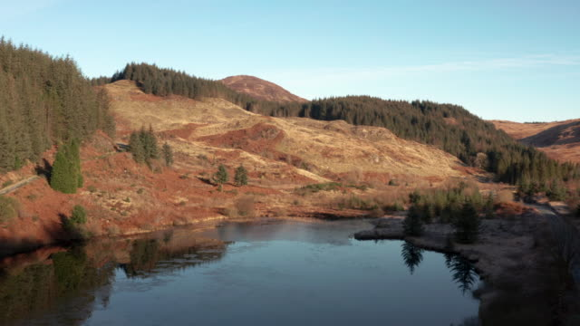 vídeos de stock e filmes b-roll de aerial view of the edge of a scottish loch in dumfries and galloway on a bright autumn morning - margem do lago