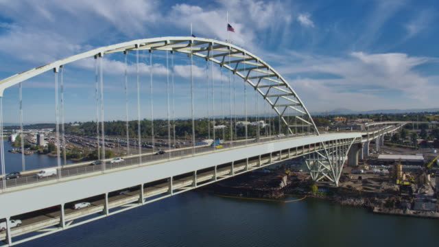 Aerial View of the Fremont Bridge with flags flying at half mast and the Willamette River with boats loading grain video