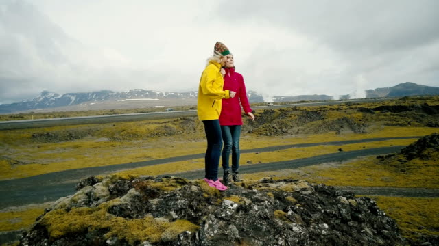 Aerial view of the friends standing on the top of mountain and dancing of happiness. Two woman in lava field in Iceland